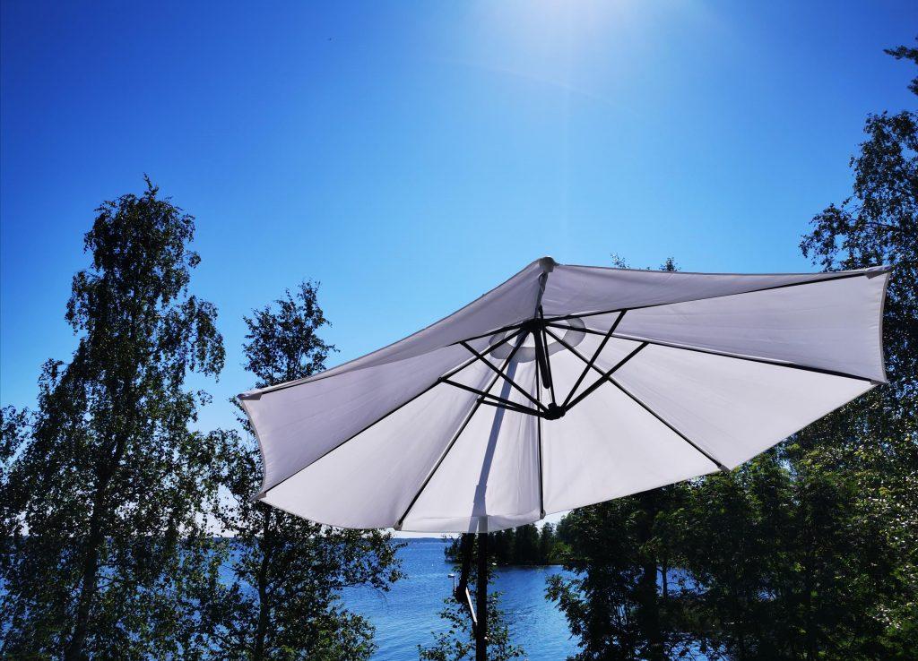Valkoinen auringonvarjo avoinna, taustalla sininen taivas, järvi ja puita.