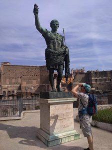 Kädellään ylöspäin viittaavan keisarin patsas Roomassa. Taustalla näkyy kaivauksissa esiinotettuja kivimuureja.